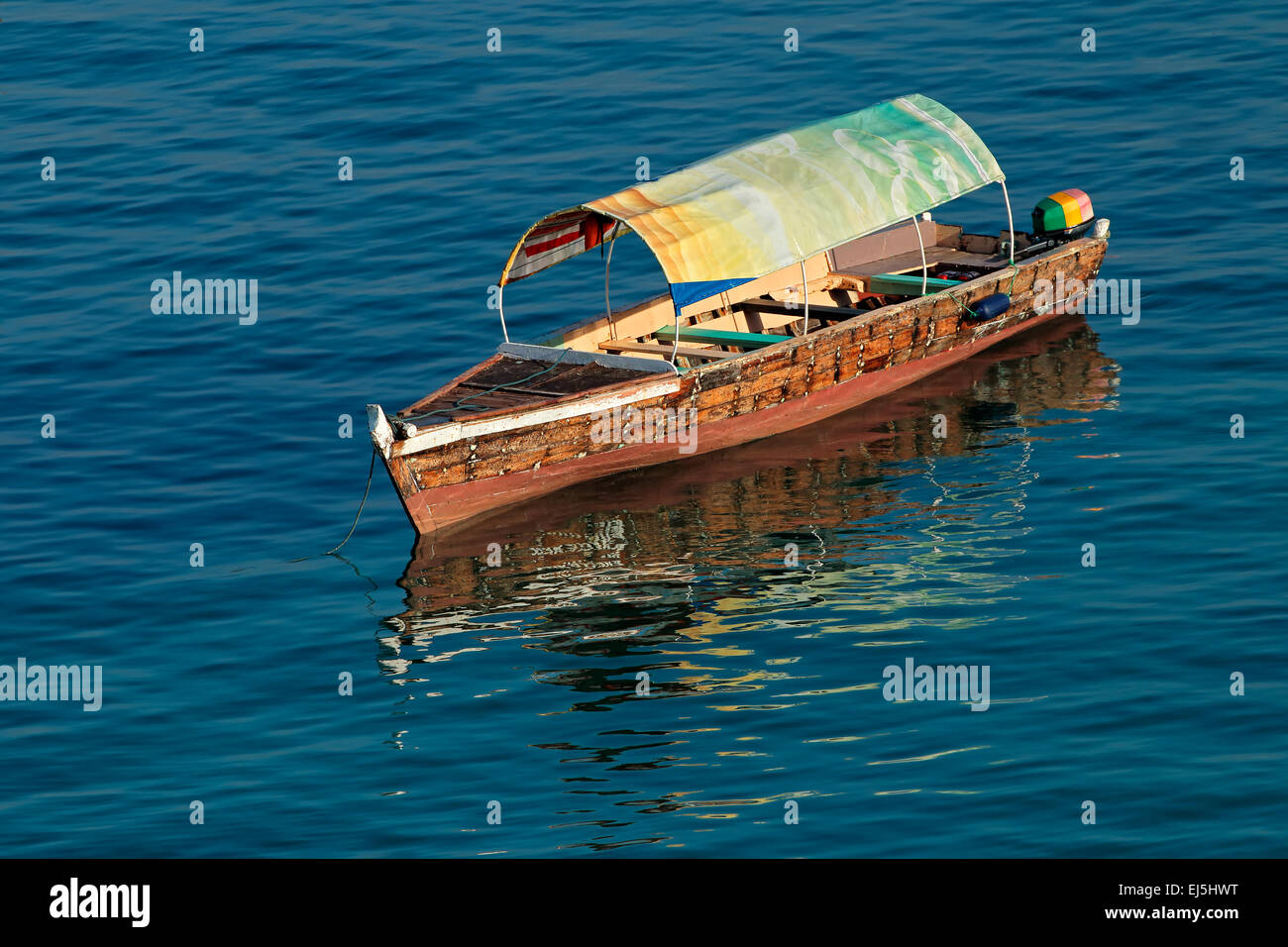 Anchored wooden boat with reflection in water, Zanzibar island - Stock Image
