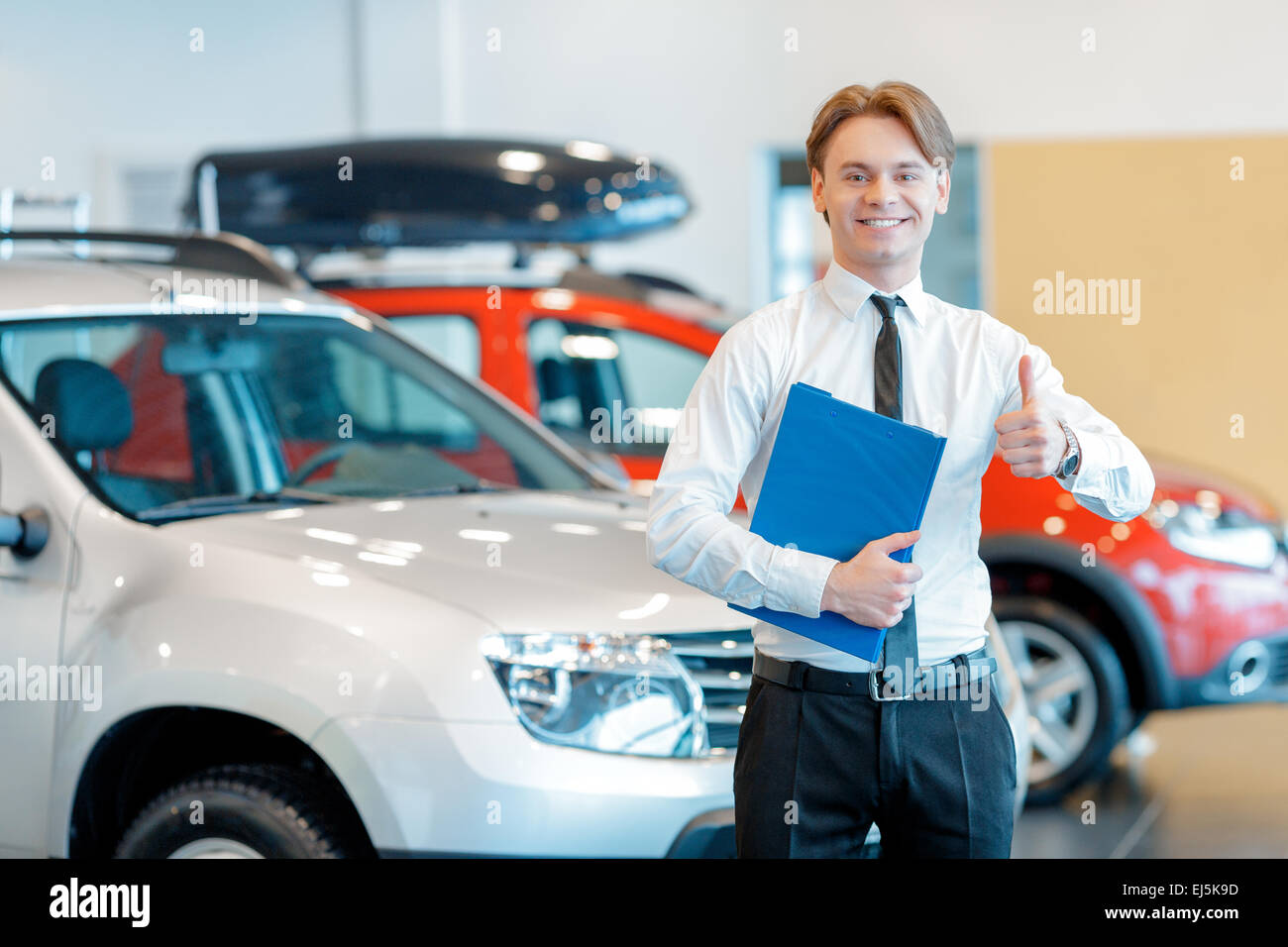 Young smiling salesman with clipboard in car dealership - Stock Image