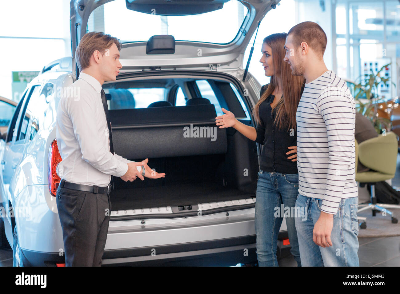 Salesman displaying trunk of the car to customers - Stock Image