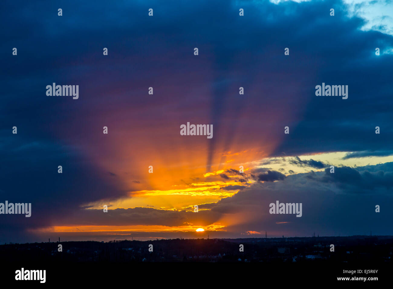 Dramatic sunset, dark clouds - Stock Image