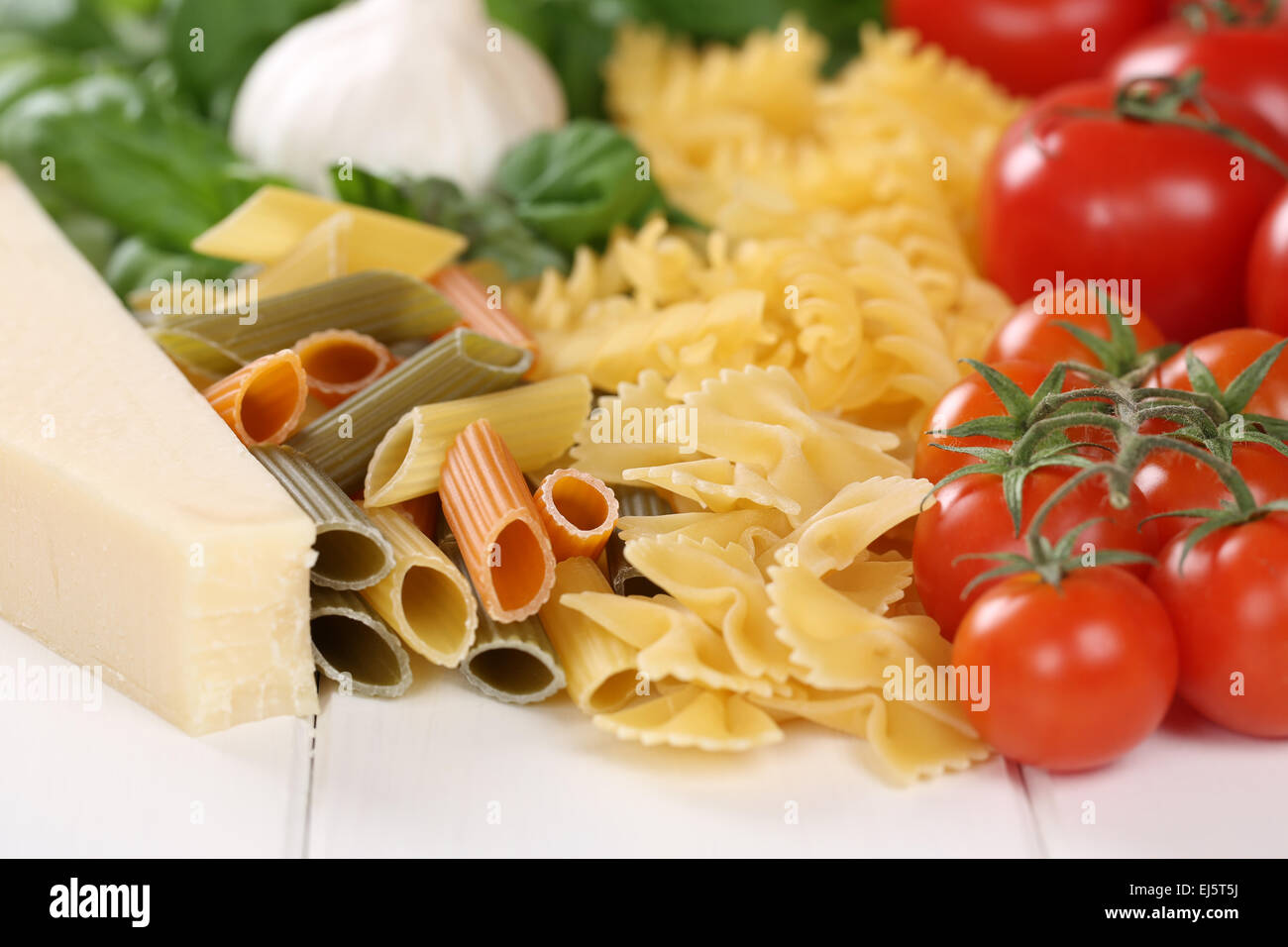 Ingredients for a Pasta noodles meal with tomatoes, penne, basil and Parmesan cheese - Stock Image