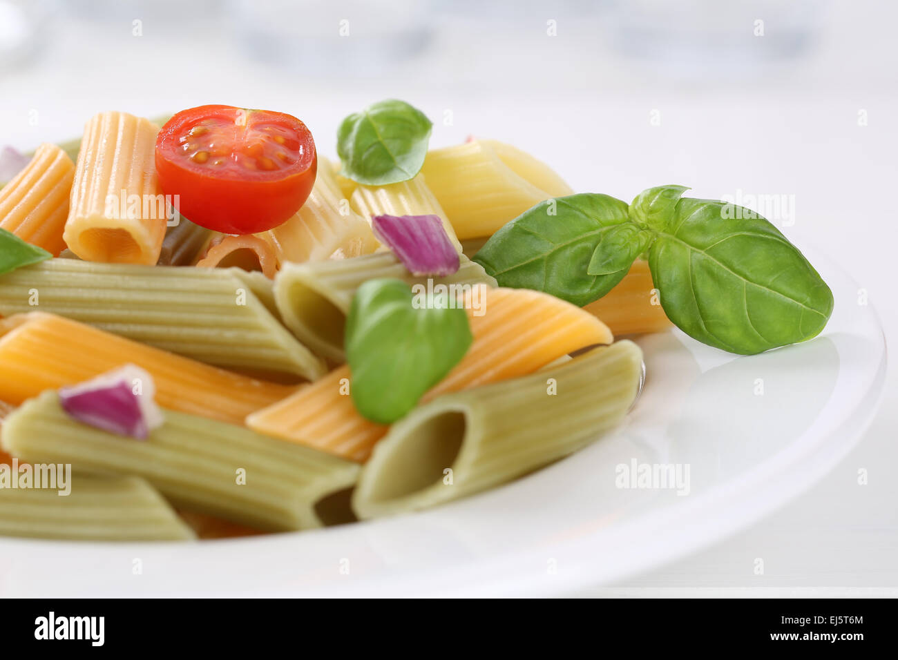 Colorful Penne Rigate noodles pasta meal with tomatoes on a plate - Stock Image