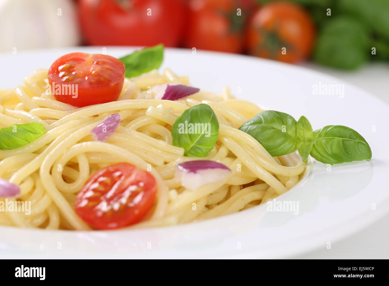 Spaghetti noodles pasta food meal with tomatoes and basil on plate - Stock Image