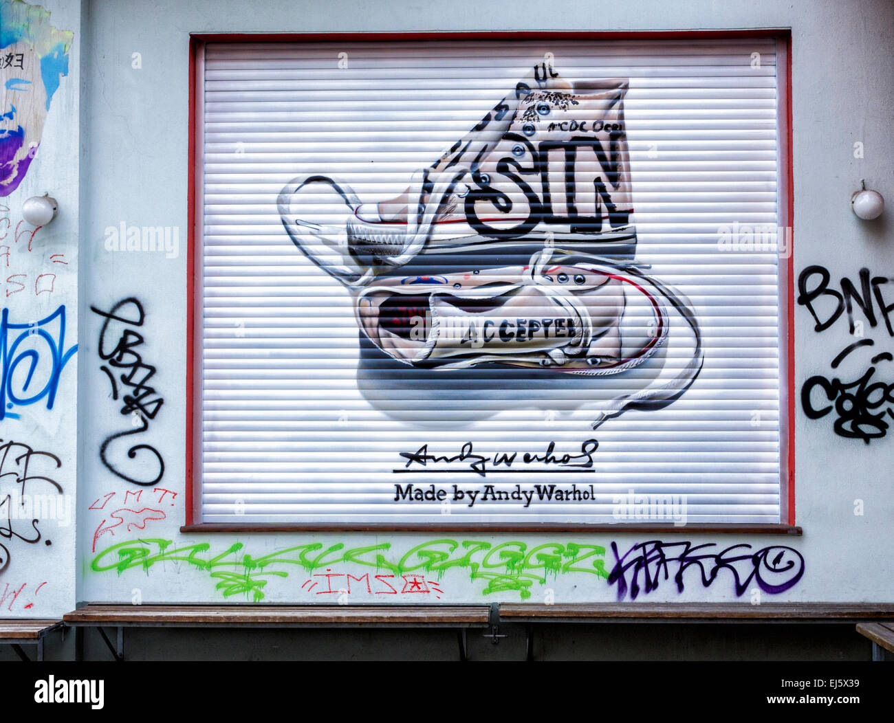 Advertisement for Converse trainers, chucks named after Chuck Taylor amongst graffiti on shop blind, Mitte Berlin - Stock Image