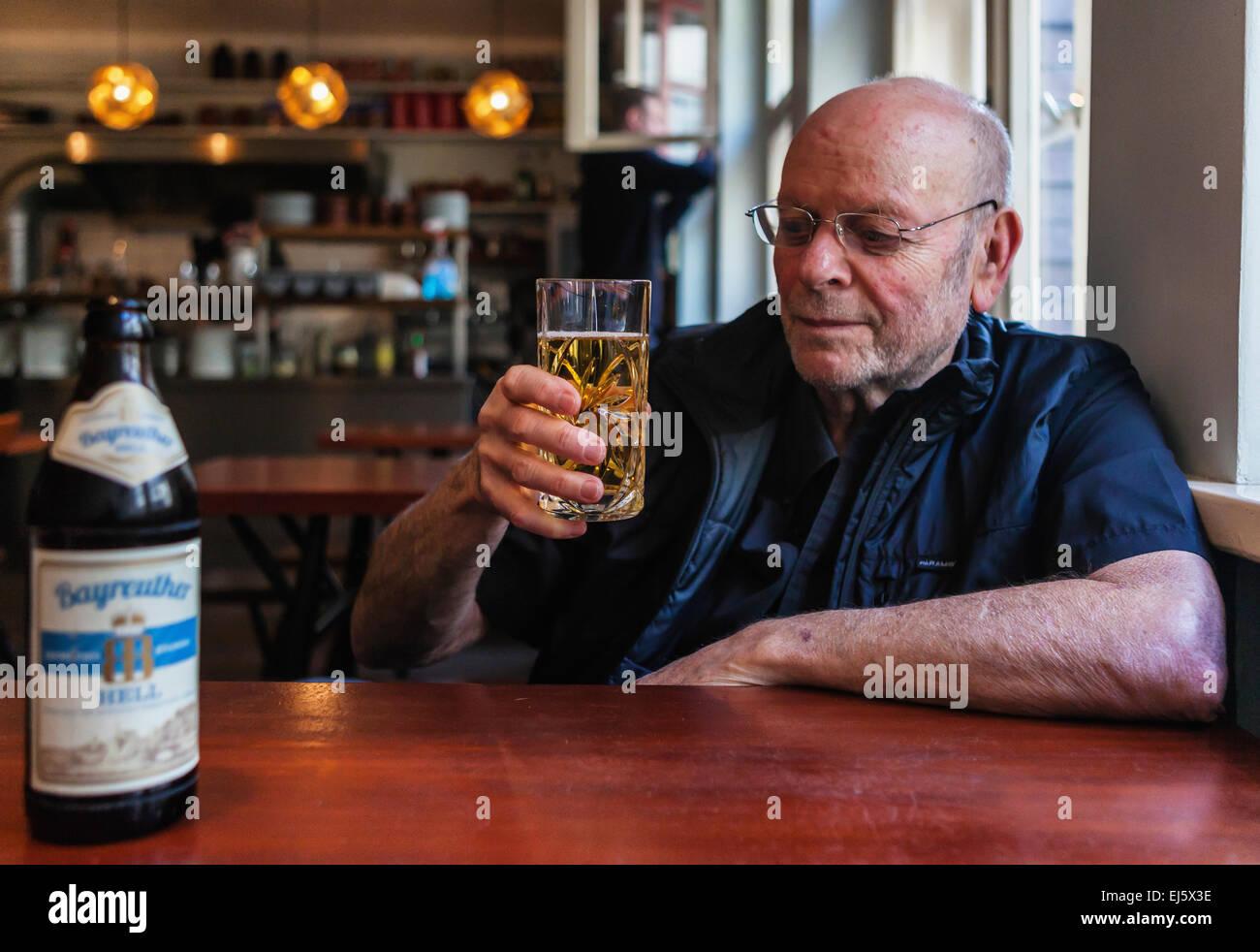 Elderly senior man drinking German beer in Mogg and Melzer restaurant interior, Auguststrasse, Mitte, Berlin - Stock Image