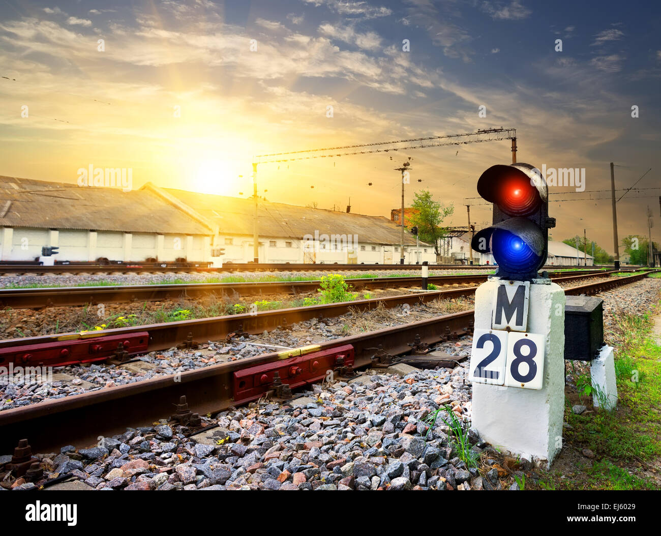 Railway semaphore near industrial station at sunset - Stock Image