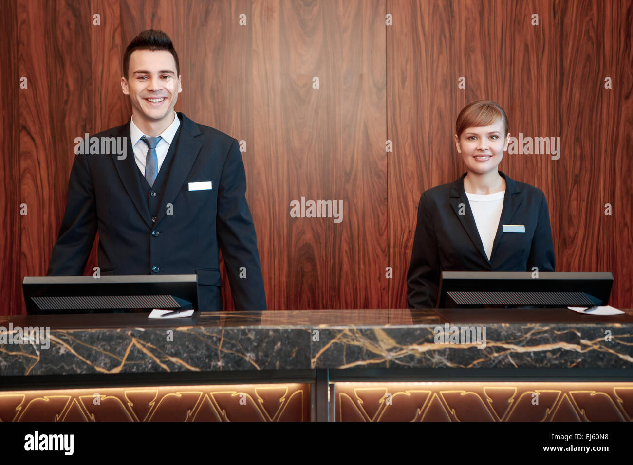 Hotel receptionists behind the counter - Stock Image