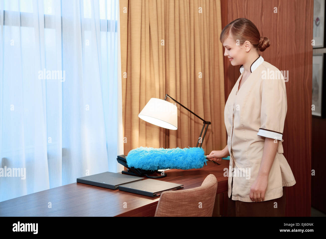 dusting furniture. Hotel Maid Dusting Furniture - Stock Image O