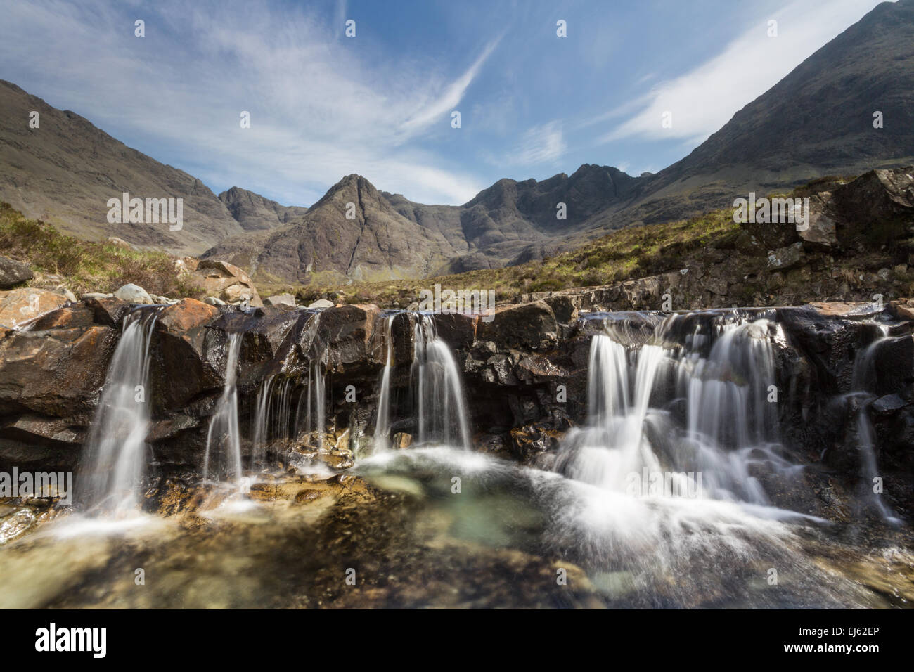 A cascade of waterfalls into a pool amongst the Fairy Pools under the Cuillin Mountains on the Isle of Skye, Scotland - Stock Image
