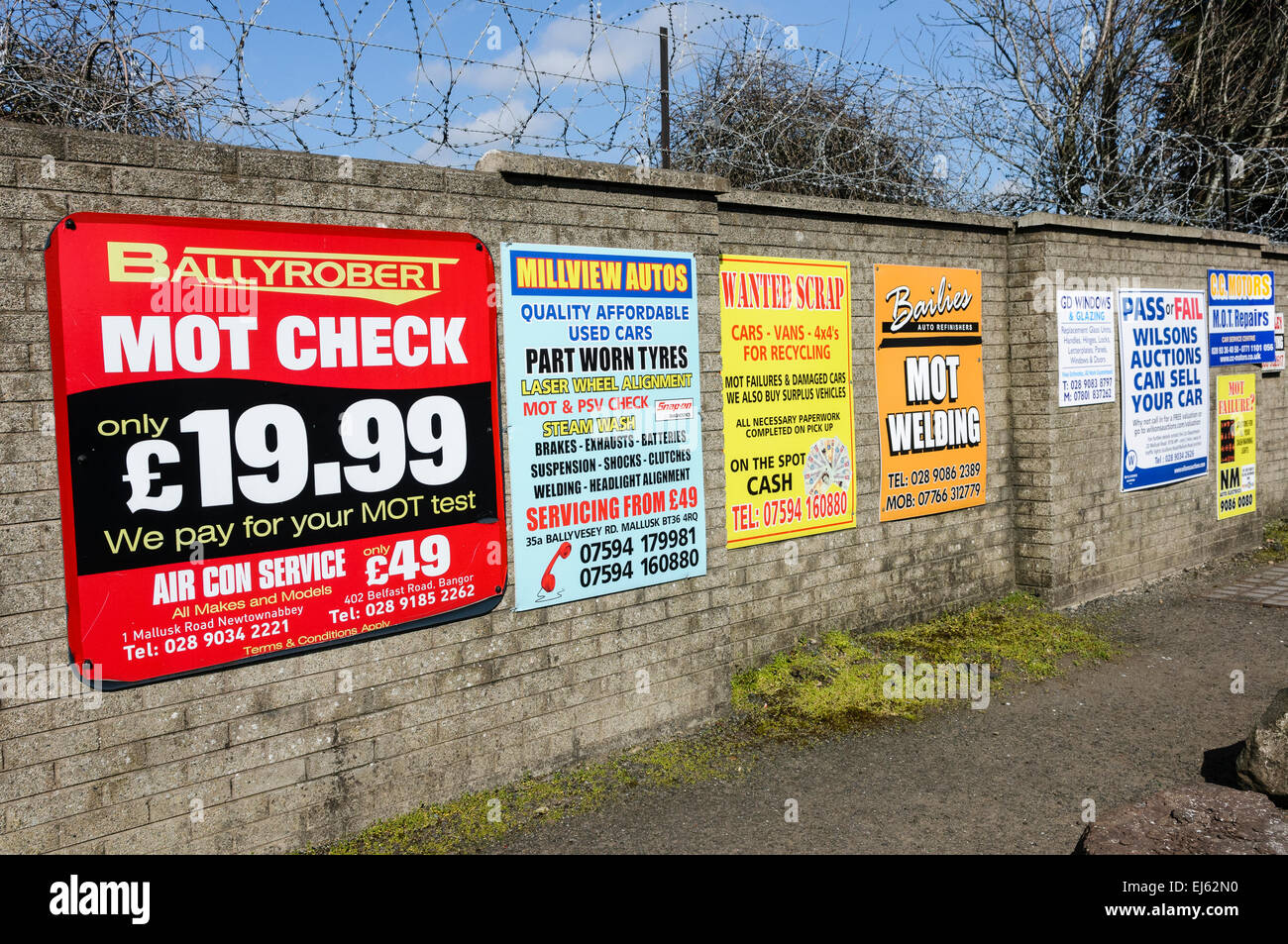 Signs outside a MOT Testing Centre offering welding services, tyres, repairs and scrappage. - Stock Image