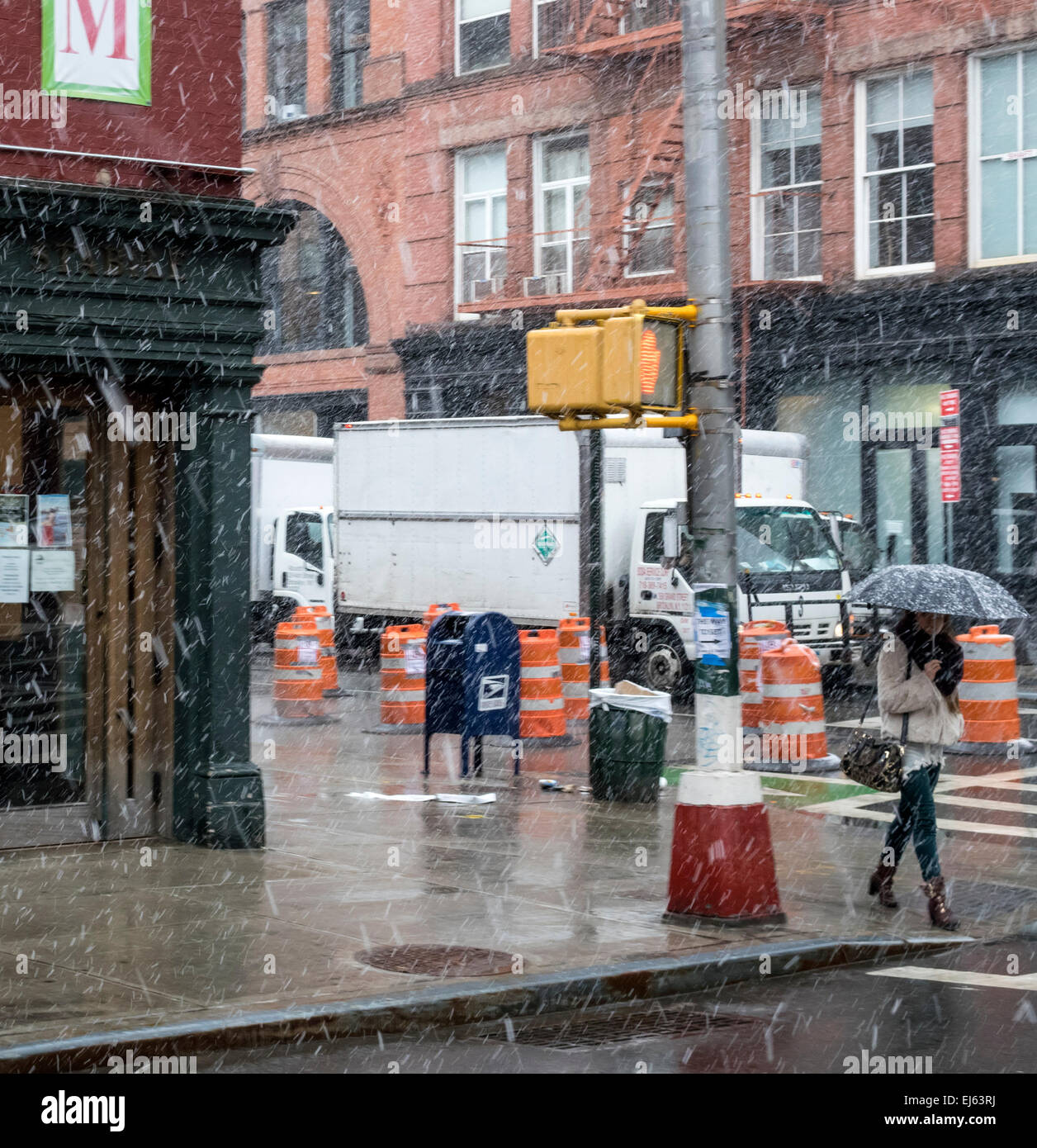A young woman with an umbrella walking in a light snow fall in Lower Manhattan - Stock Image