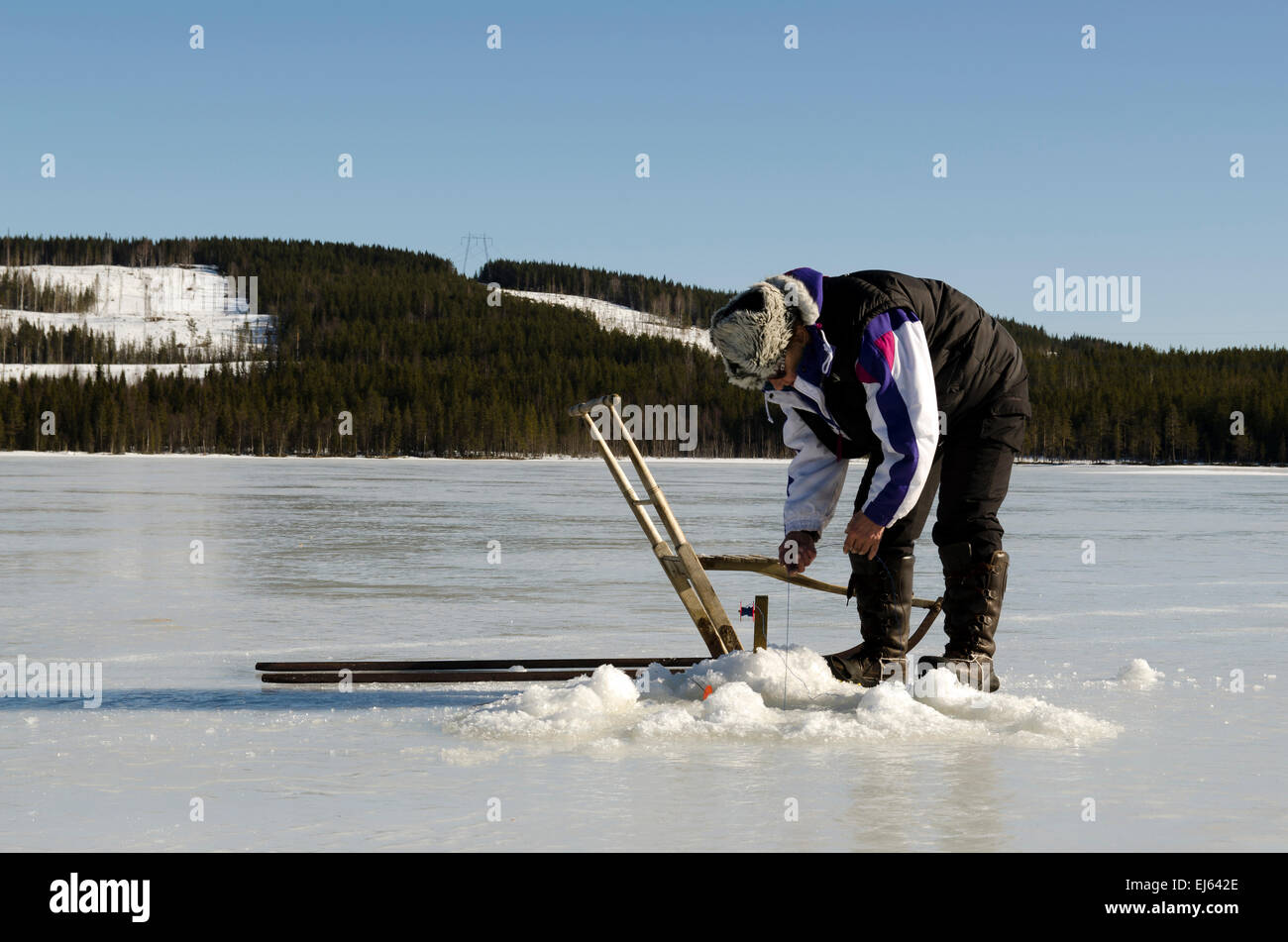 Women from North of Sweden checking if some fish is stuck on the hook, and with a special vehicle for use on ice. - Stock Image