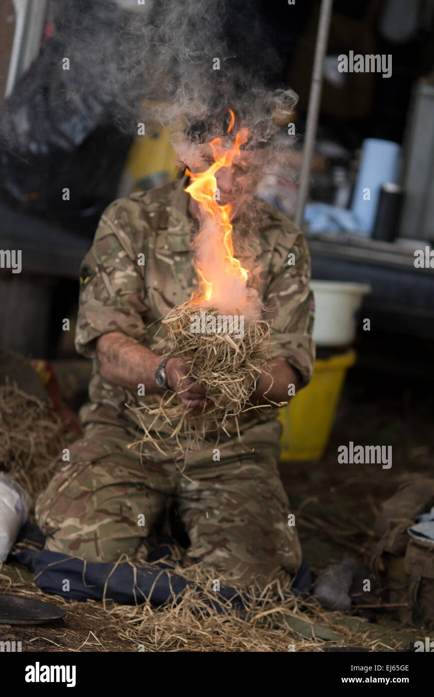 Royal Marine Association demonstrating how to make fire in a survival scenario - Stock Image