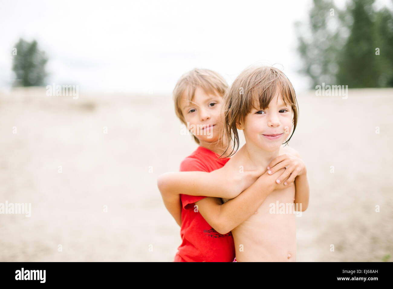 185783fd70ce88 Cute happy fraternal twins enjoying their time at the beach. Brother and  sister hugging.