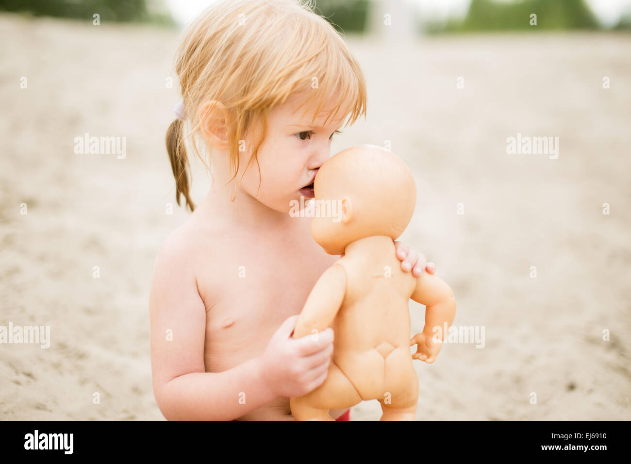 Toddler Girl Kissing Baby Doll At The Beach On Hot Summer Day Baby Playing On Sand