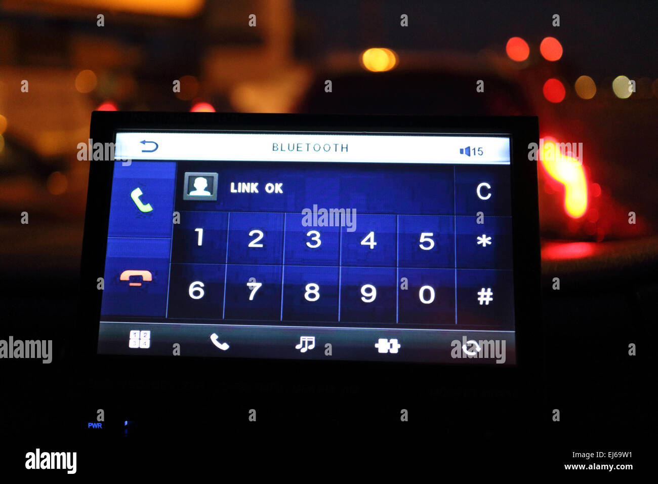 bluetooth mobile phone link screen in vehicle dashboard in traffic at night - Stock Image