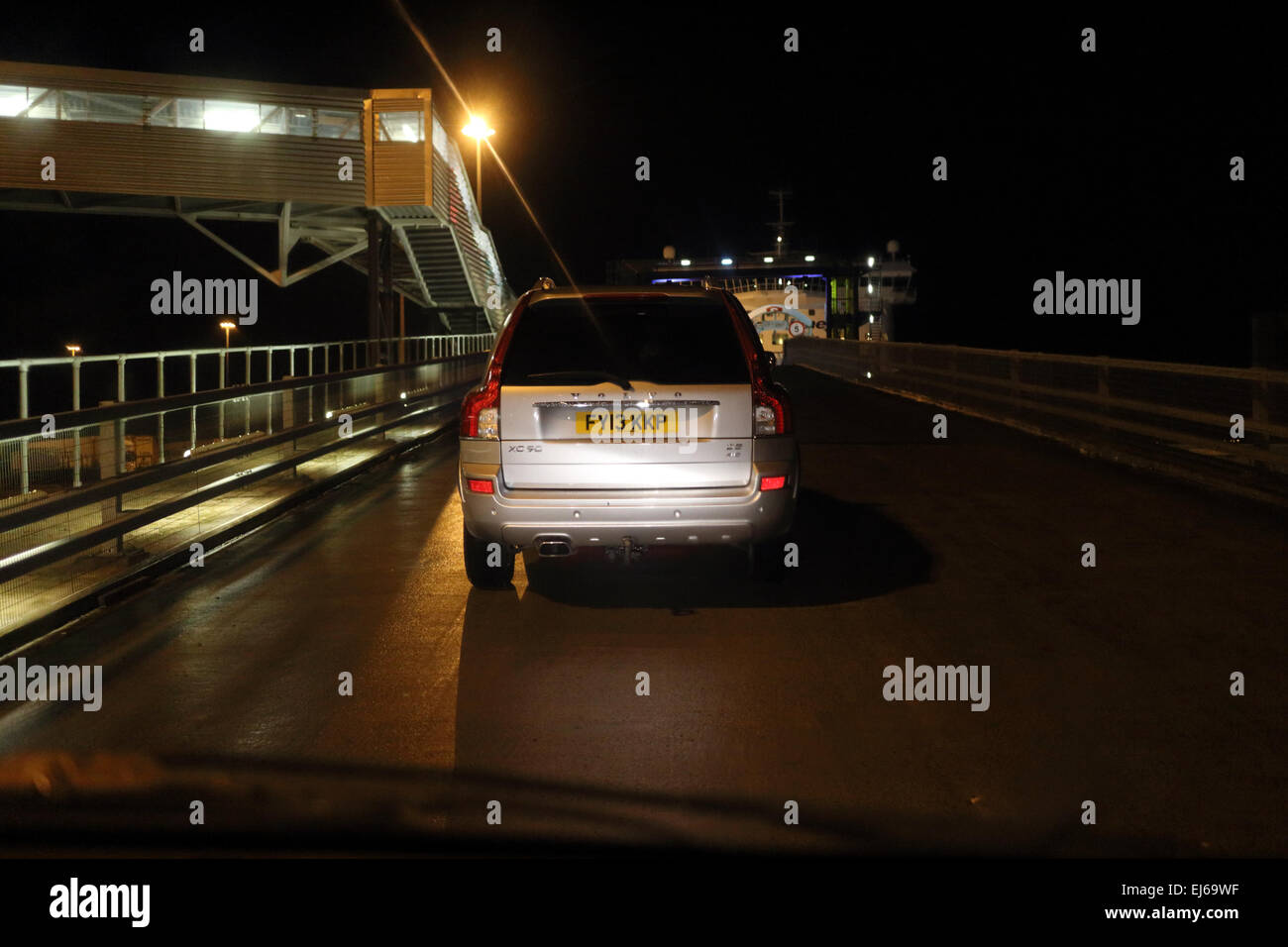 cars driving up loading ramp to ferry in the port of belfast - Stock Image