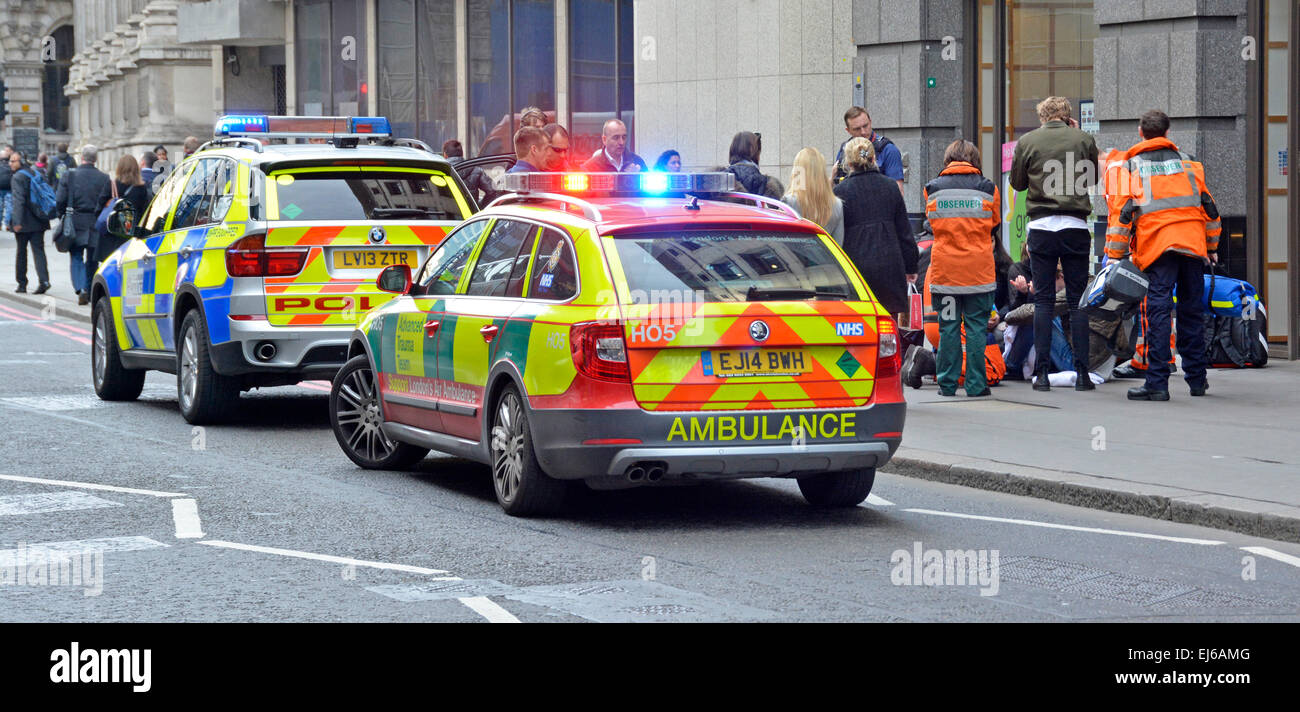 Medics and police with onlookers around a pedestrian on pavement requiring medical assistance with parked emergency - Stock Image
