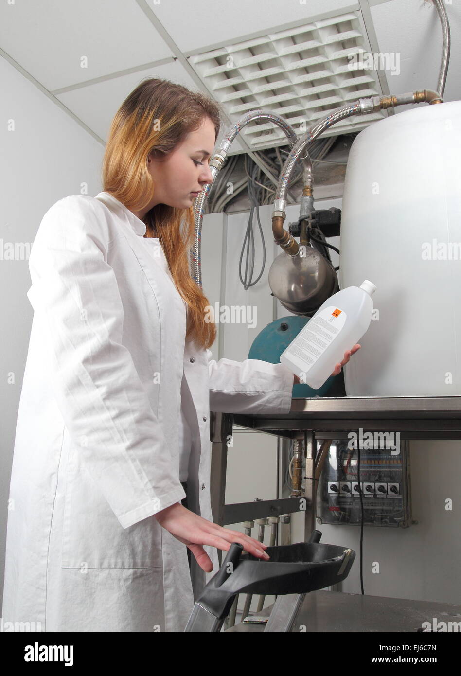 A Woman at a  plant with chemicals - Stock Image