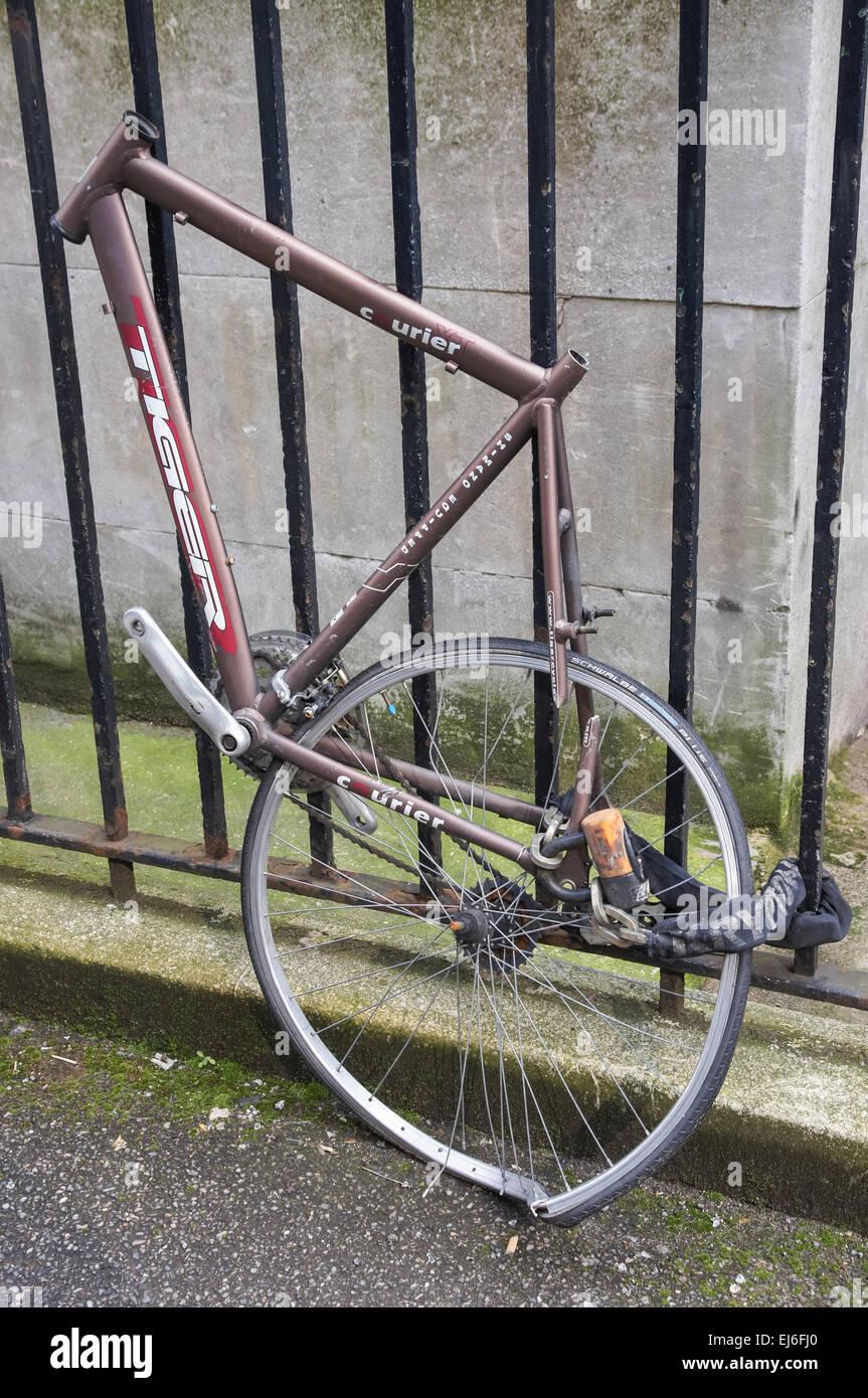 Damaged bicycle locked to fence, London England United Kingdom UK - Stock Image