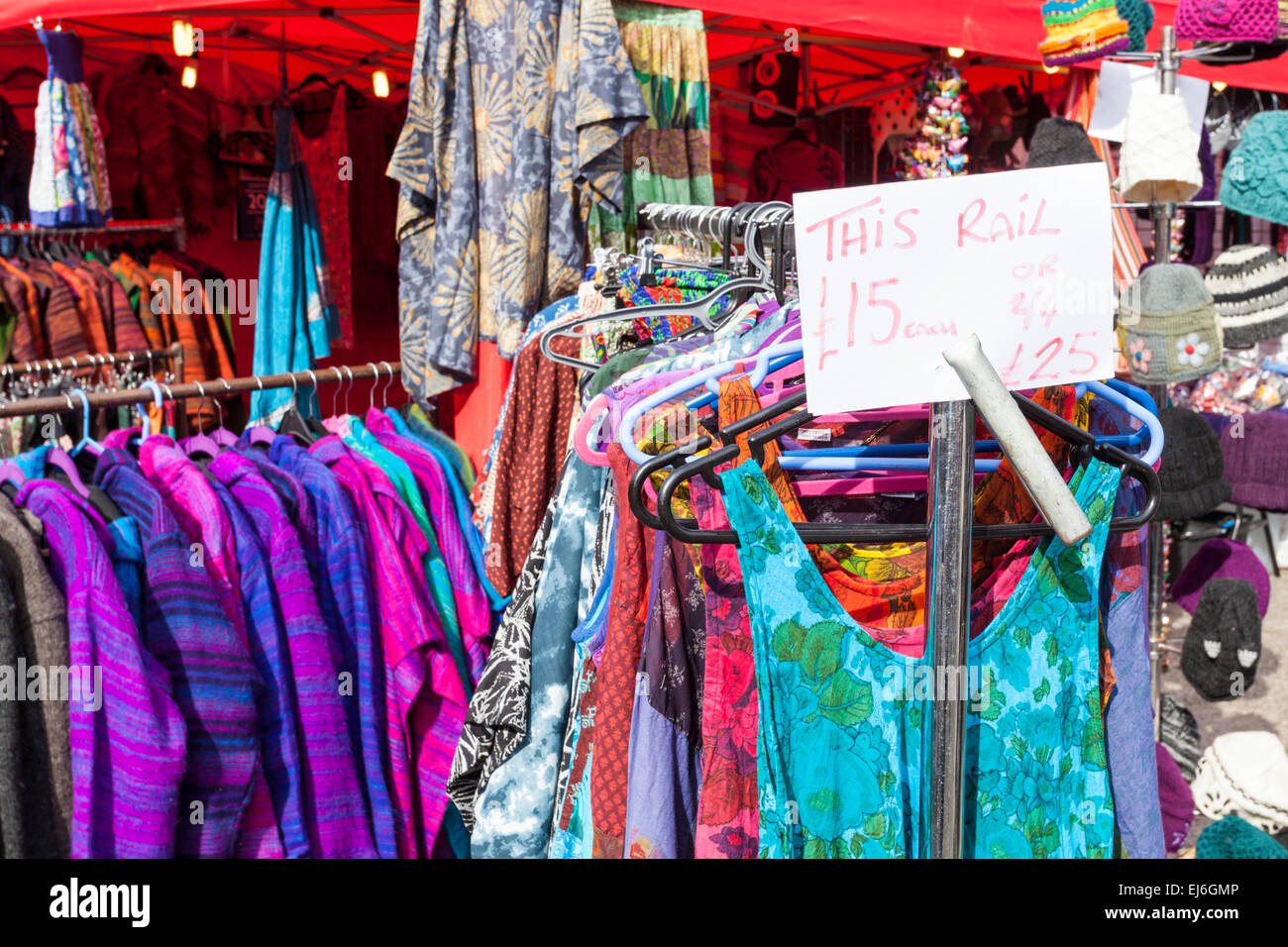 Dress rail with dresses for sale with a price ticket showing cheap prices for clothes on a clothing stall at a market, - Stock Image