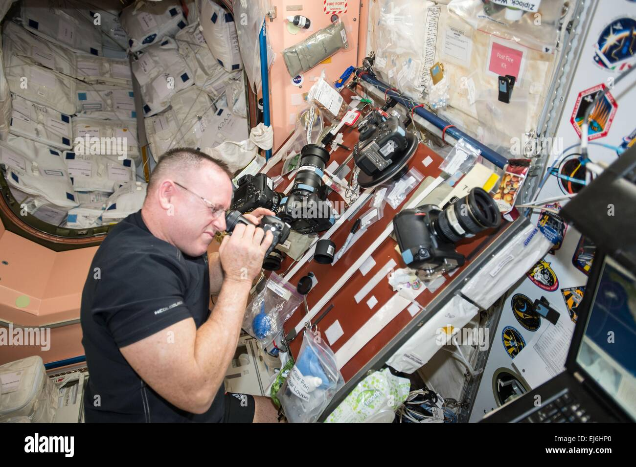 US astronaut Barry Wilmore inspects one the Nikon cameras aboard the International Space Station in preparation - Stock Image