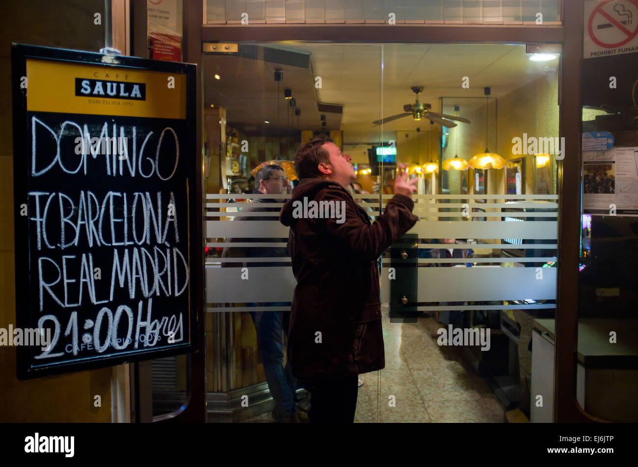 March 22, 2015 - Barcelona, Spain.   In Barcelona a soccer fan look the TV through the window of a bar during the - Stock Image
