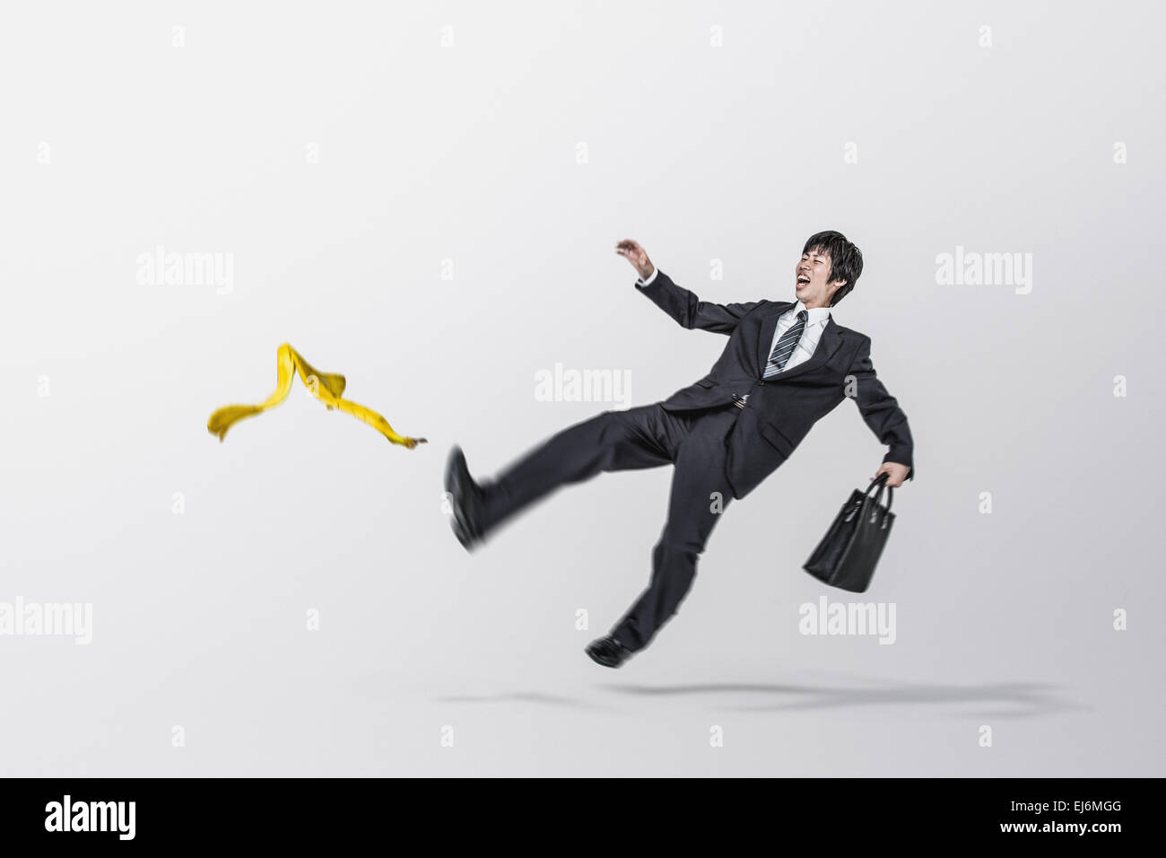 Young Japanese businessman slipping on a banana - Stock Image