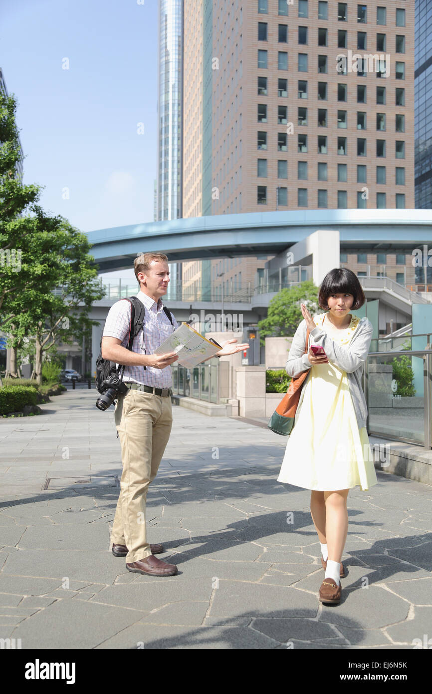 Young Japanese girl escaping from foreign tourist asking for help - Stock Image