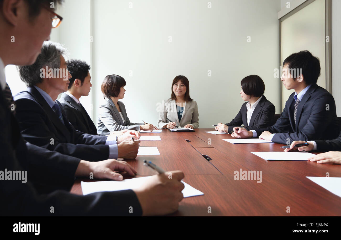 Japanese business people attending board meeting - Stock Image