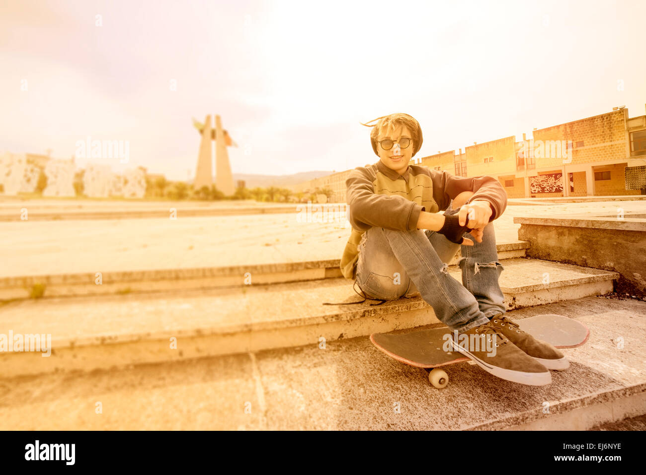 young rasta guy outdoor sitting on his skate with a warm filter applied - Stock Image