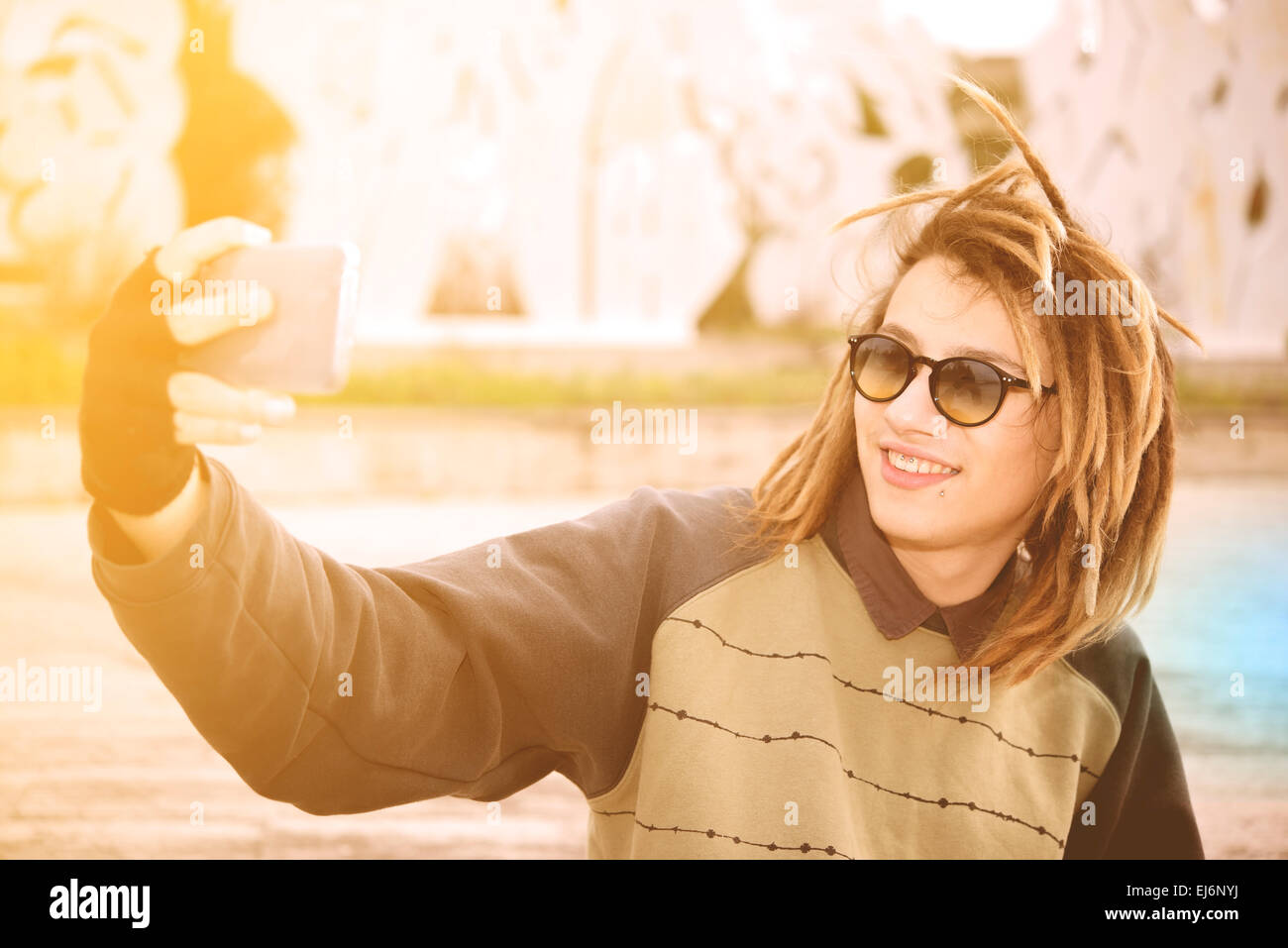 portrait of young guy outdoor with rasta hair smiling with smart phone in a lifestyle concept with a warm filter - Stock Image