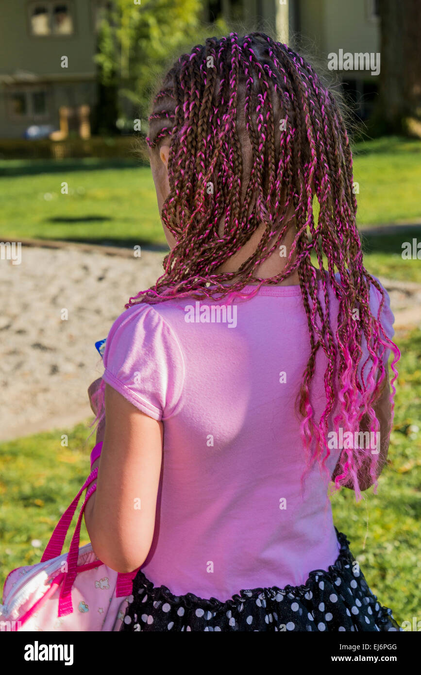 Girl with pink ribbon braided into hair. - Stock Image