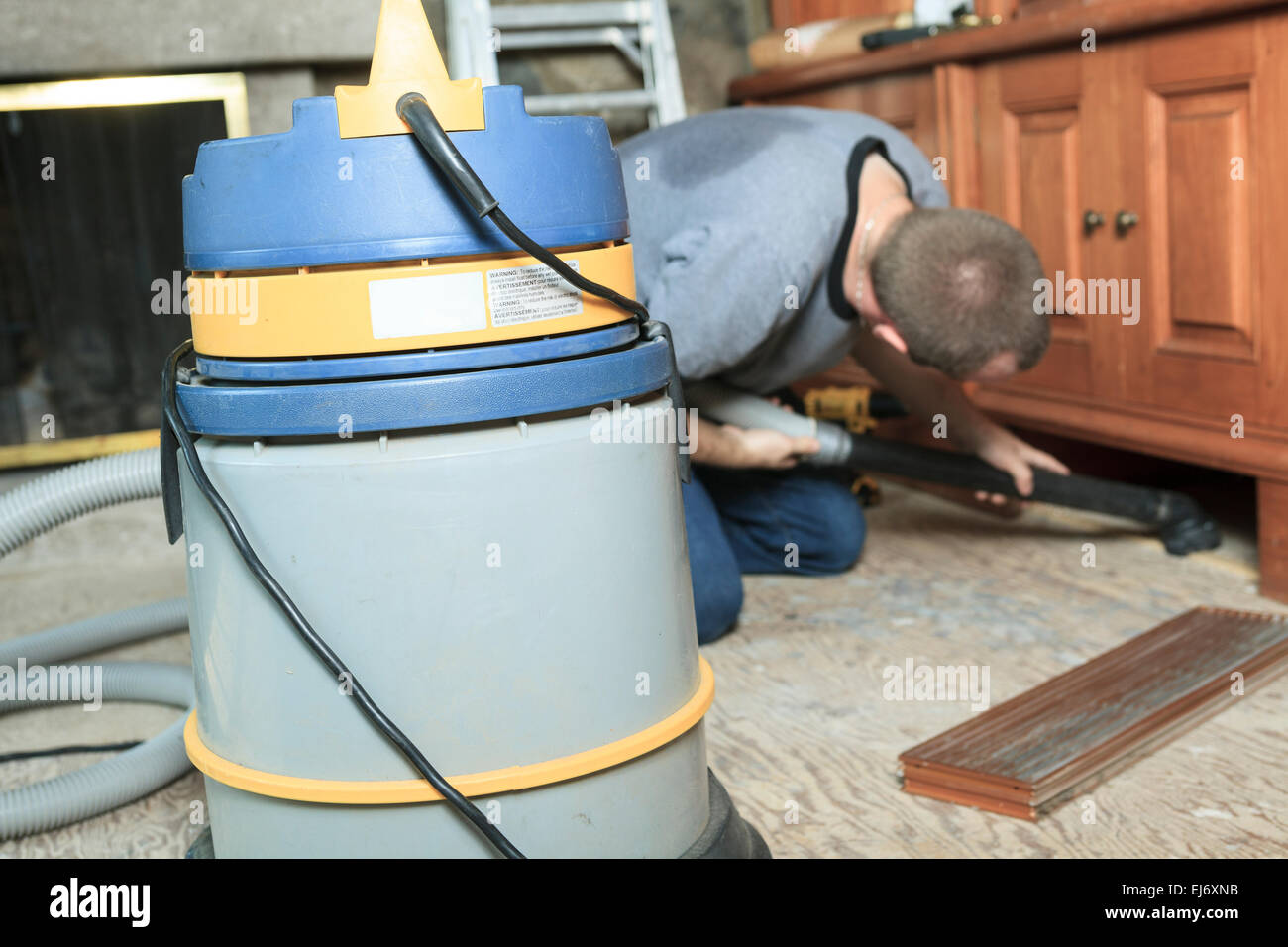 worker vacuum system trying to clean something. - Stock Image