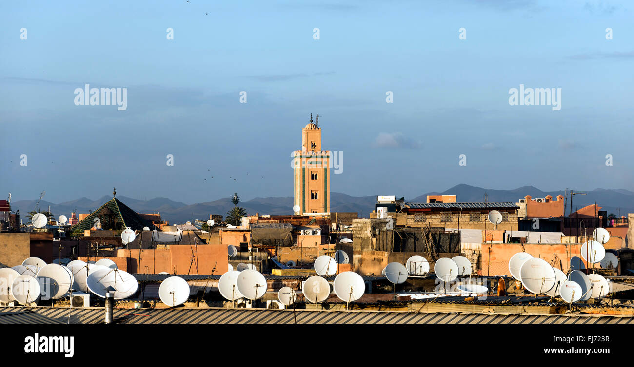 View across the roofs with satellite dishes to a minaret and the Atlas Mountains, Marrakech, Morocco - Stock Image