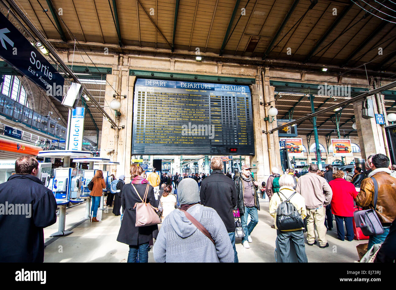 Travellers standing in front of the large departure times board at the Gare Du Nord train station in Paris, France. - Stock Image
