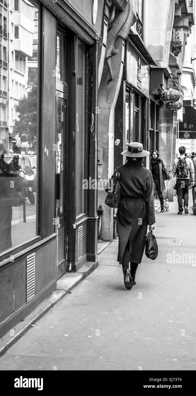 A chic Parisian woman in a lovely coat and hat with good quality bags strolls through the streets of the Marais - Stock Image