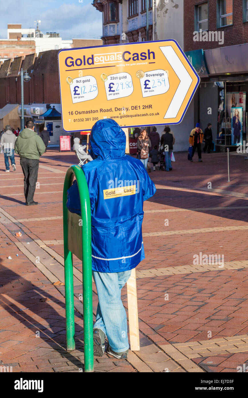 Low paid job. Unskilled work as a sign waver. Worker holding an advertising board for Gold Equals Cash, Derby, England, - Stock Image