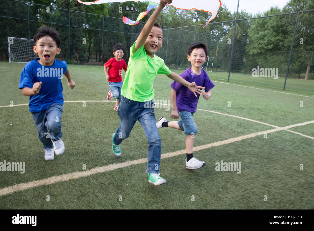 The boys are flying kites in the grass - Stock Image