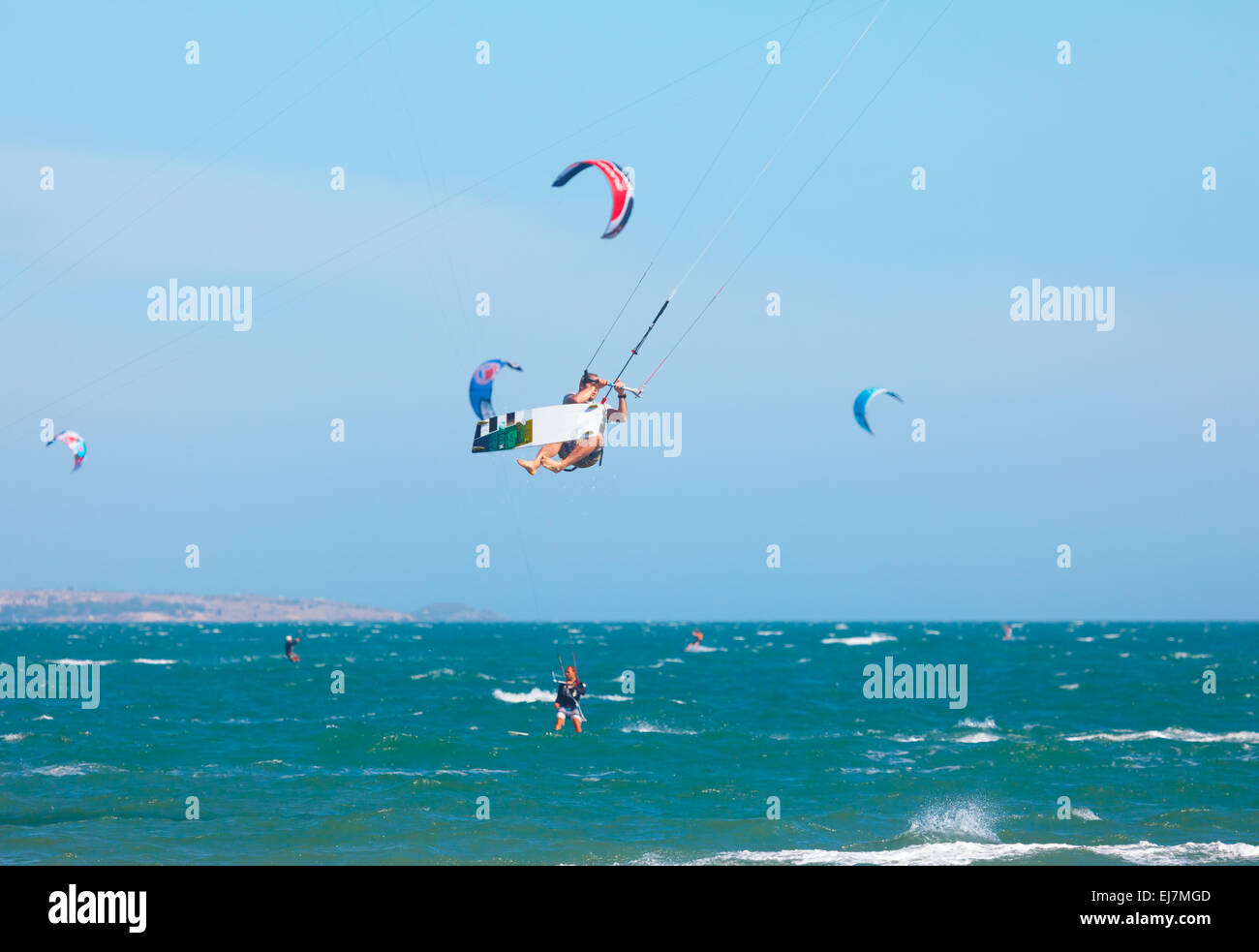 Kitesurfers riding the waves - Stock Image