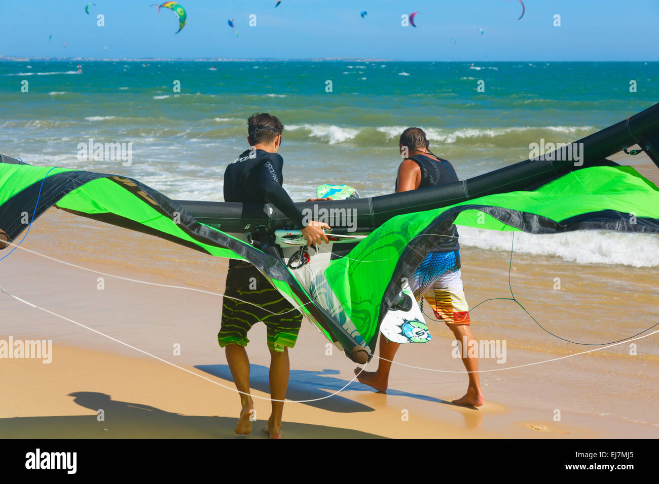 Kitesurfers on the beach - Stock Image