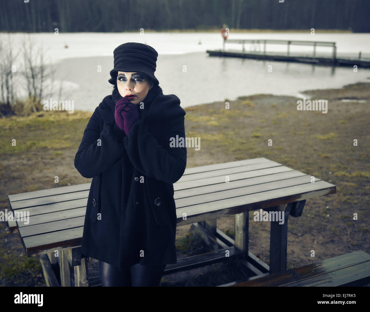 Fearful fashion woman wearing a winter coat and hat and she posing in a wintry beach, cold rainy weather, cross processed image Stock Photo