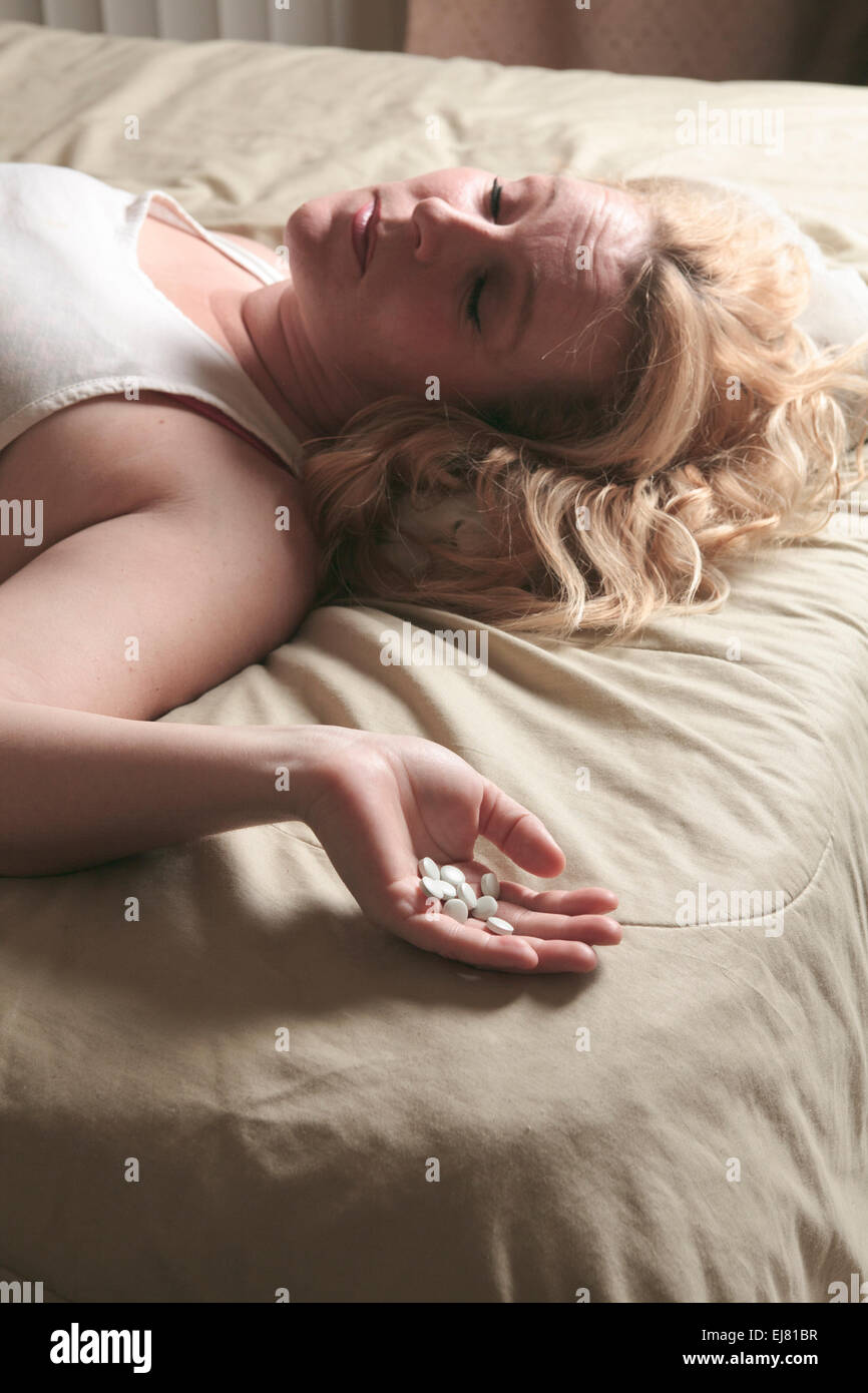 A sad woman taking medication on bed. - Stock Image