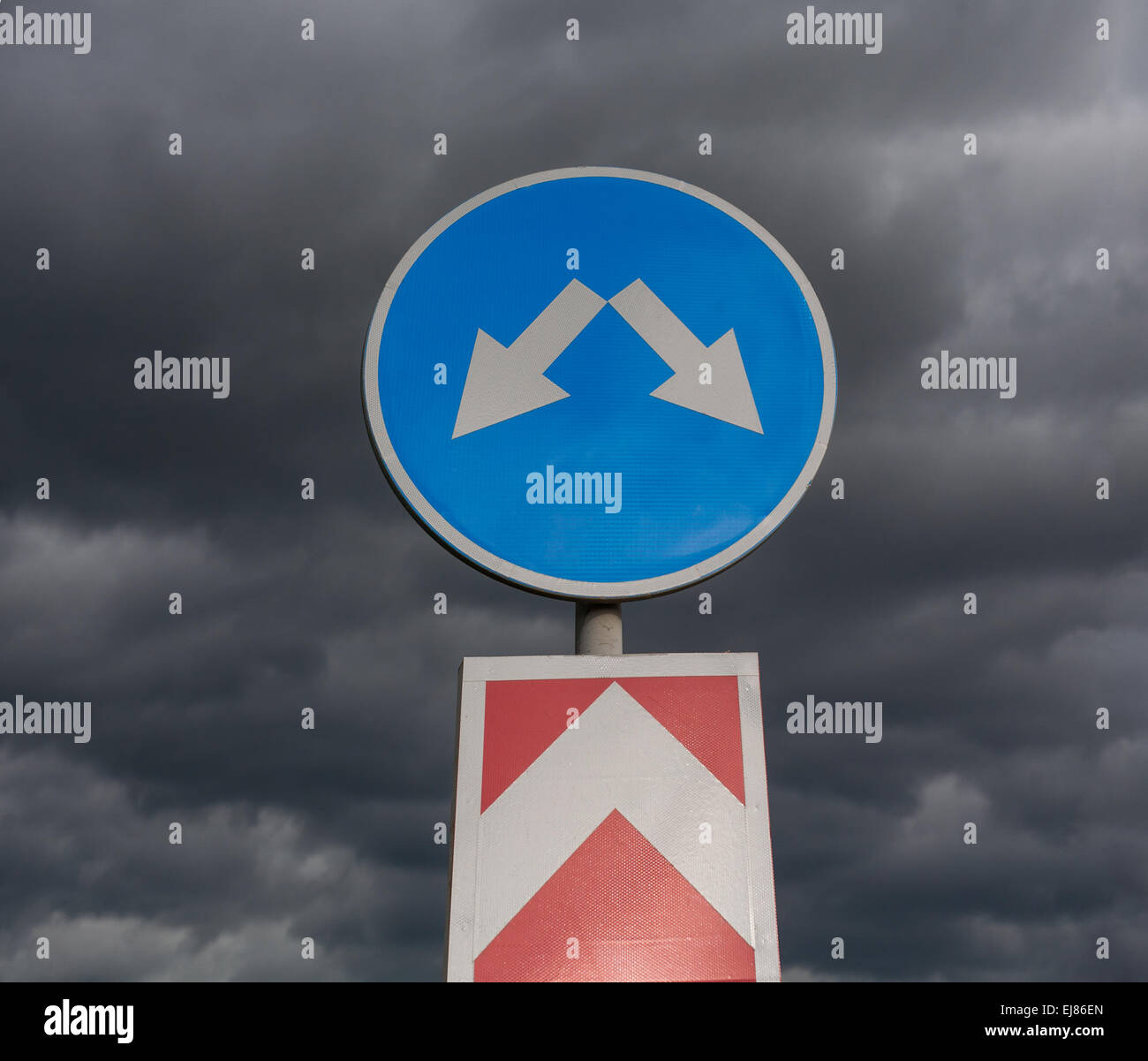 Road sign against cloudy sky Stock Photo