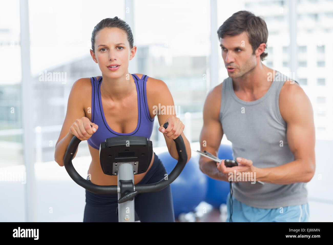Trainer watching woman work out at spinning class Stock Photo