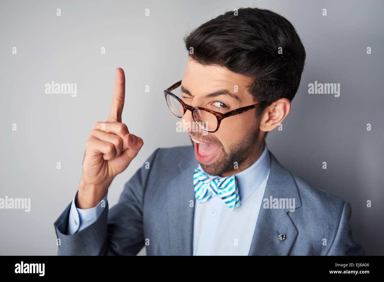 Funny young man with glasses and jacke winking - Stock Image