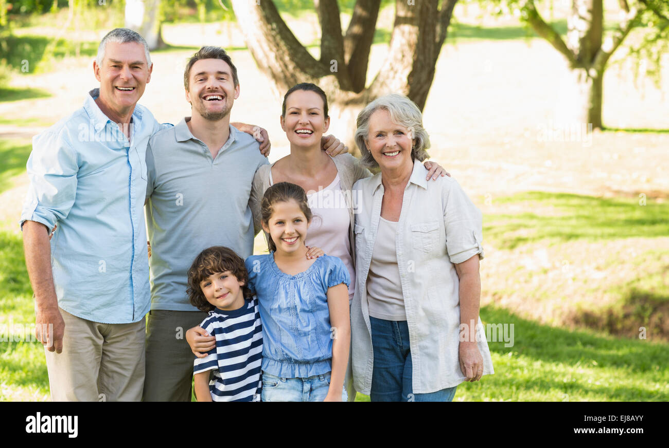 Portrait of a happy extended family in park - Stock Image