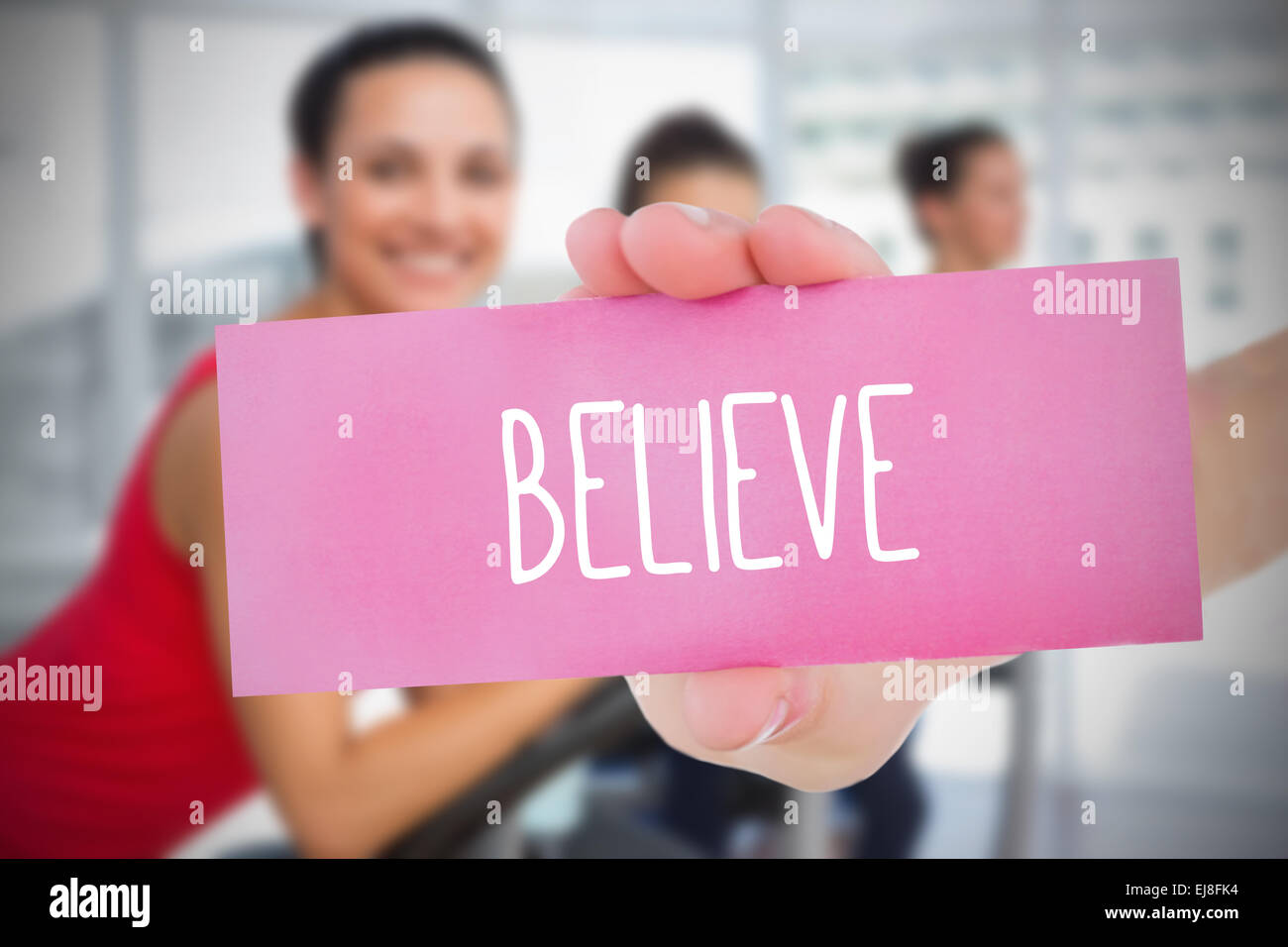 Woman holding pink card saying believe - Stock Image