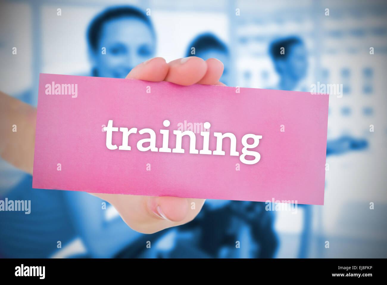 Woman holding pink card saying training - Stock Image
