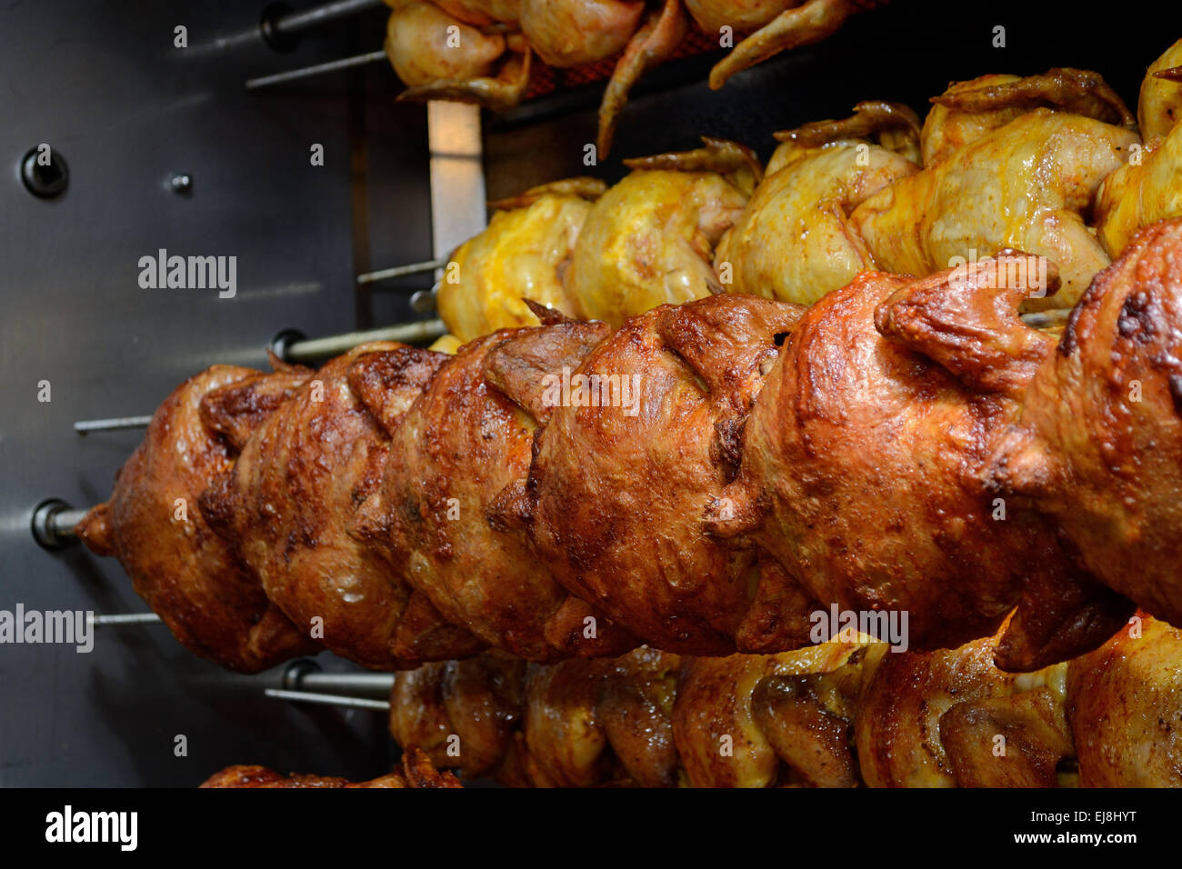 Poultry meat rotates on chicken griller - Stock Image